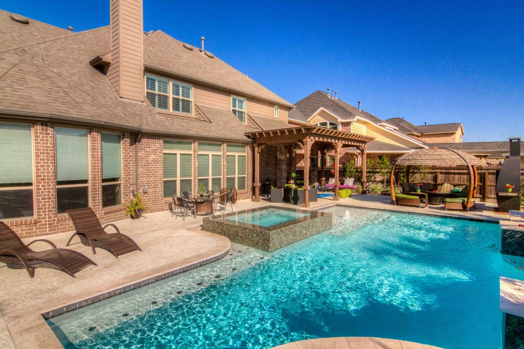 photograph of exterior home Backyard with a pool