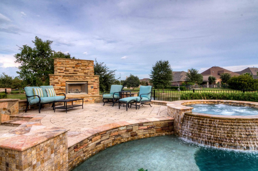 Photograph of Backyard pool with waterfall and fireplace.