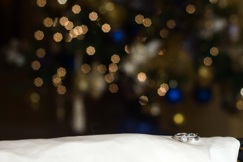 Photograph of wedding rings sitting on white cloth with lights in the background
